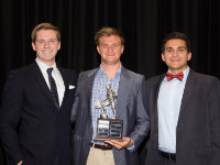 Phi Sigma Kappa's Brendan Hessler accepts an award from the brothers of Pi Kappa Alpha.