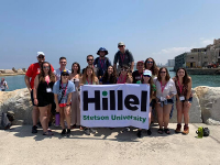 Stetson students smiling on the beach of Tel Aviv