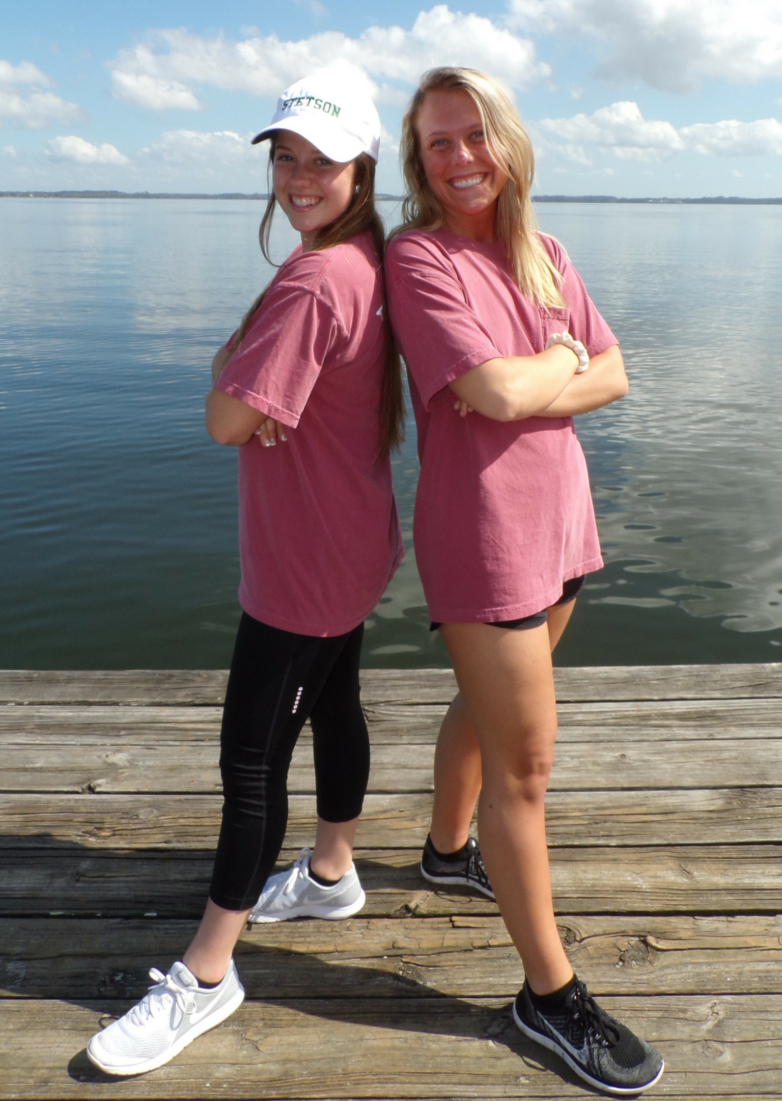 Brittani Smith and Ashley Koletsos standing back to back on a dock with a large lake behind them