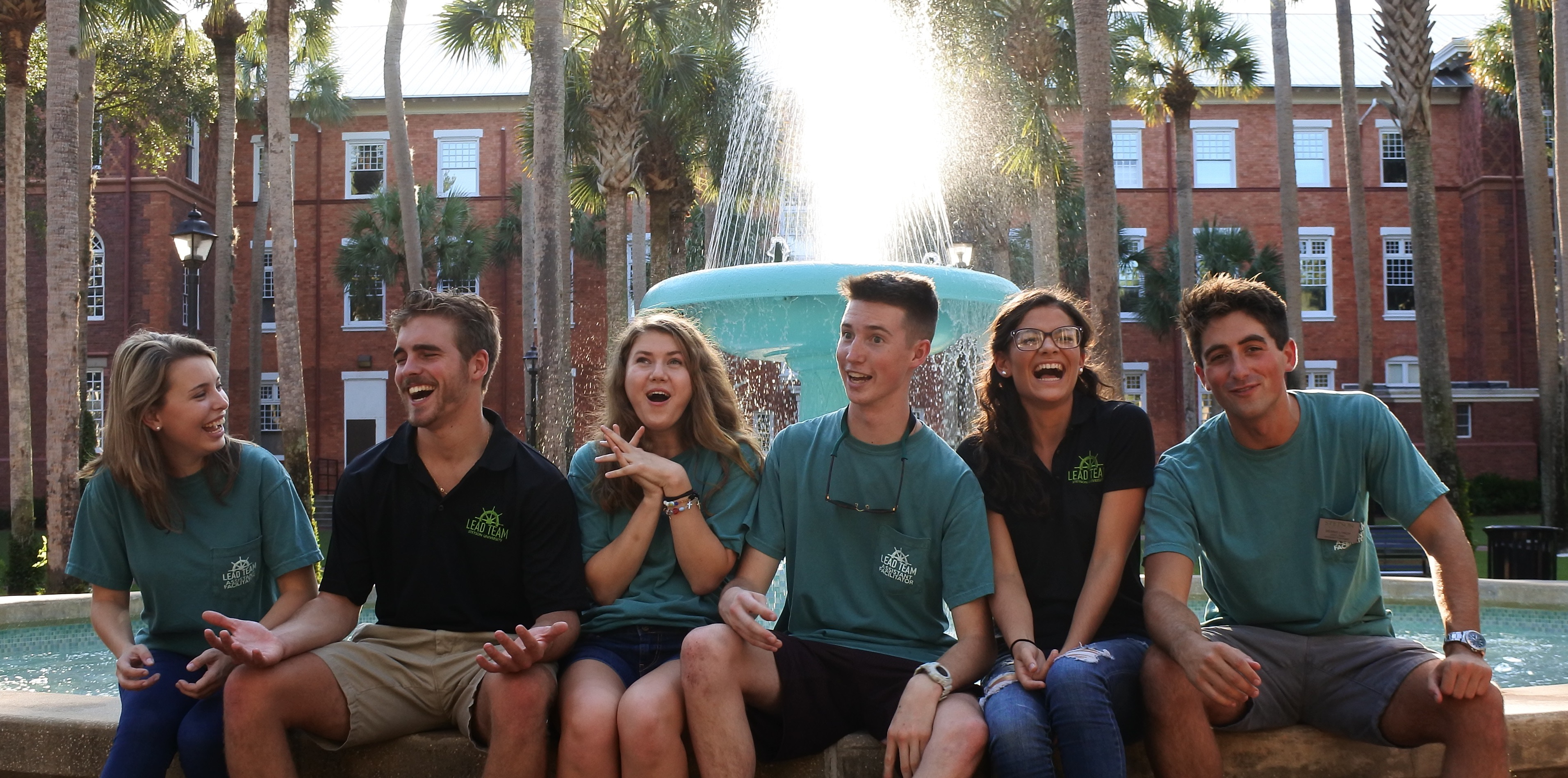 Six LEAD Team Members sitting on the fountain ledge laughing