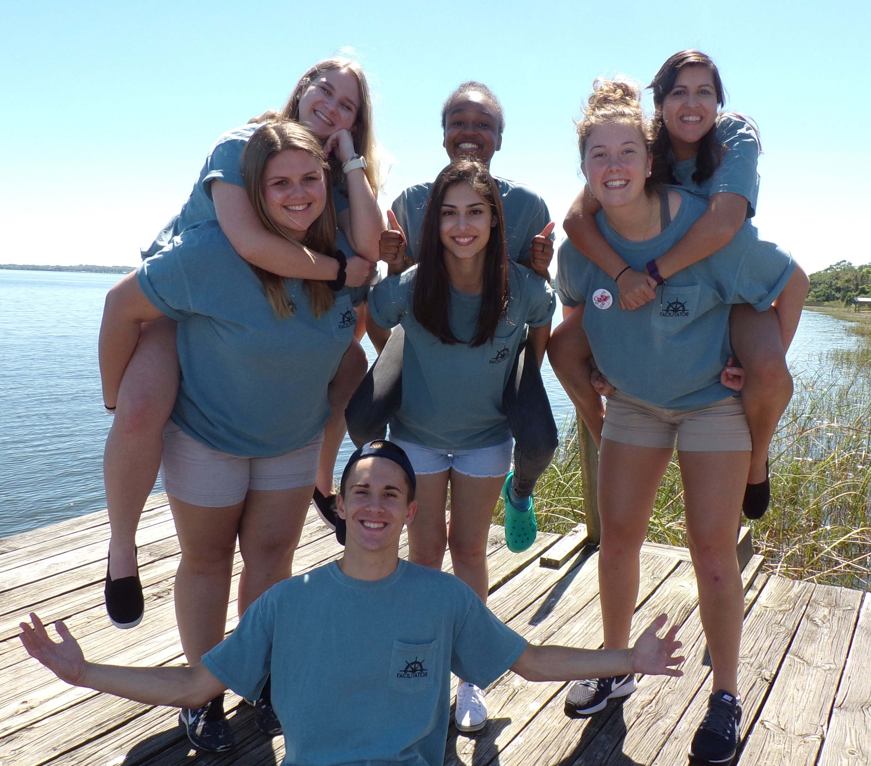Seven students wearing blue shirts on a dock. A male student is sitting with his arms up. Three female students are on the backs of the other three female students. There is a large lake behind them.