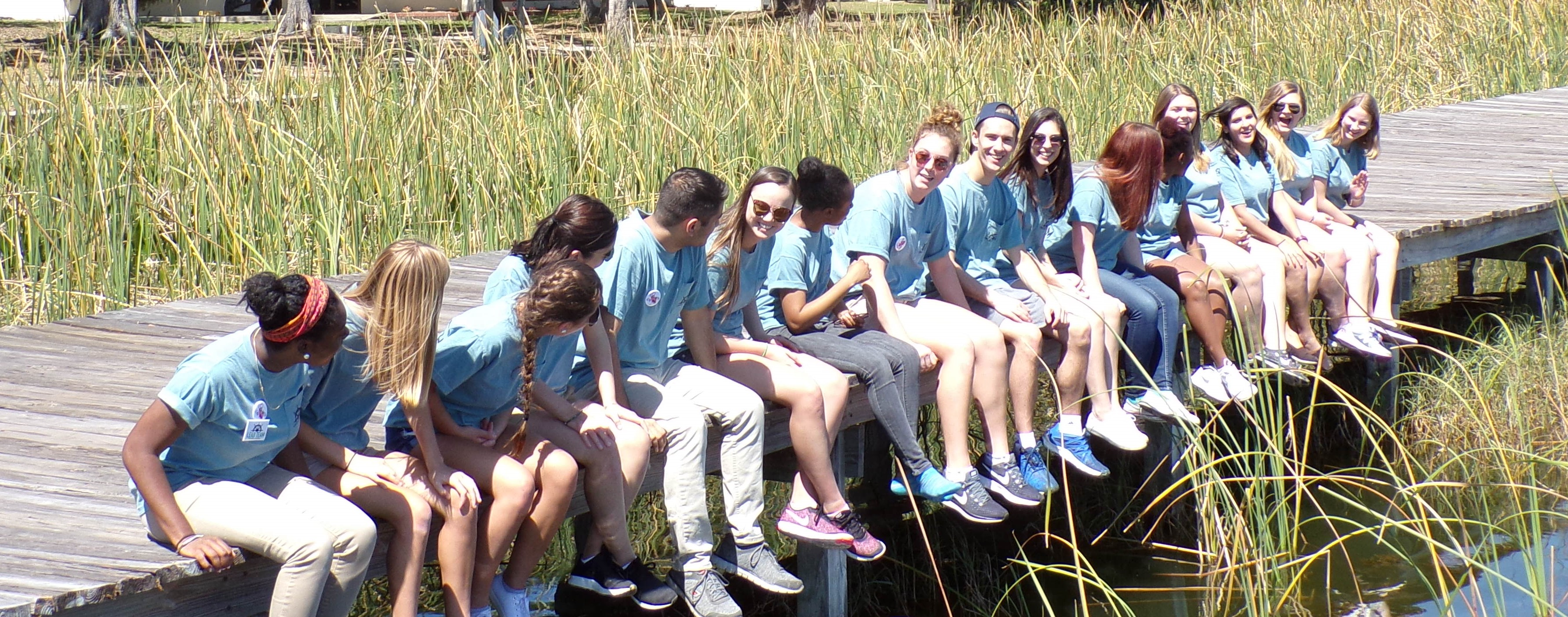 Sixteen students wearing blue shirts sitting on a dock laughing and talking