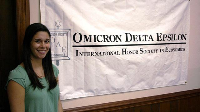 Student Beside Omicron Delta Epsilon Banner