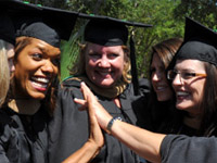 students in caps and gowns high-fiving