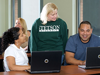instructor speaking with three students on computers
