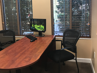 desk with computer and two chairs