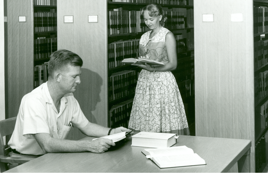 A male and a female student in the Law Library in the 1950s