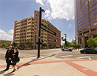 Students in formal attire walk in downtown Tampa with tall buildings