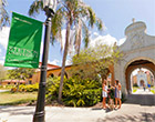 Students walk past archway of Westside Entrance on Stetson's Gulfport campus