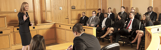 female student presents argument in courtroom before other students