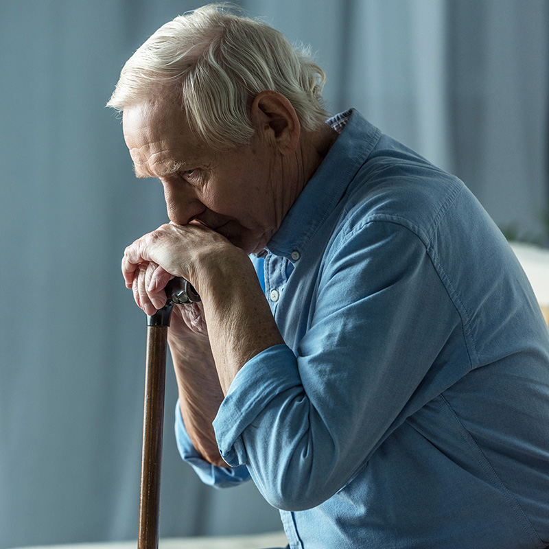 Elderly man rests his chin on his hands atop of his cane