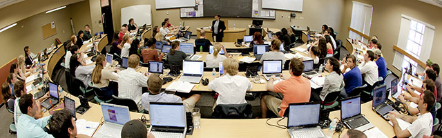 large classroom with students looking at professor