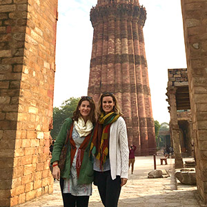 two women standing next to building in India