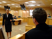 Law student questions witness within on-campus courtroom.