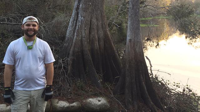 Stetson graduate Carson Zimmer stands next to creek