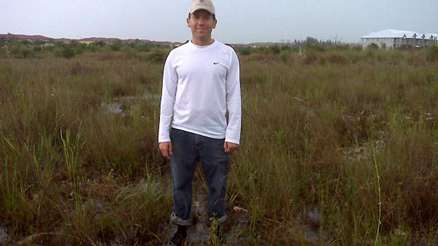 Stetson graduate standing in field