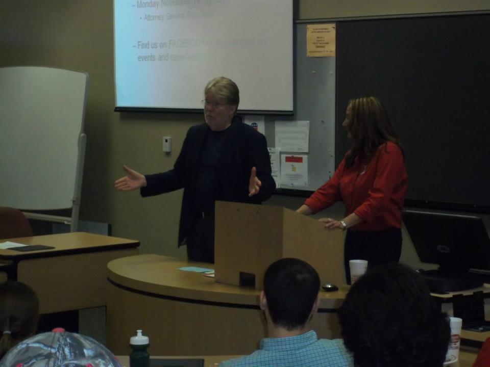 Professors Lee Coppock and Stephanie Vaughan speaking before students at meeting