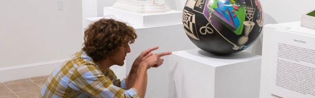 Art professor admiring a sculpture