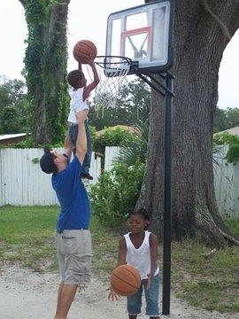 Student Helping Child Play Basketball