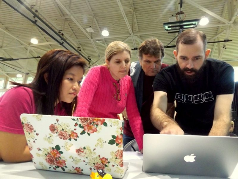 Faculty with students looking at a laptop