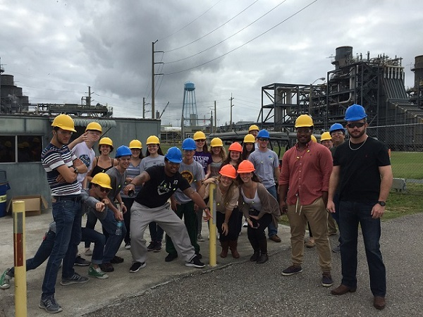 group of students and faculty at a construction site