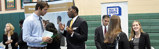 Students speaking with possible employers at a job fair in the Hollis Center Gym.