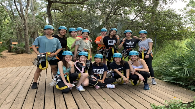 International students posing for photo after ziplining