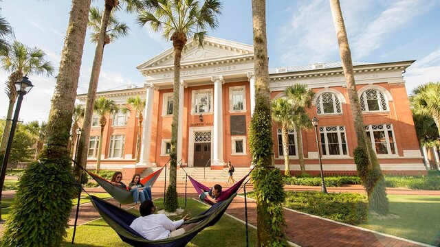 Students hammocking in front of Sampson Hall