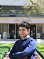 Yahia Adla standing and smiling outside duPont Ball Library